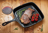 Sirloin steak with rosemary and cherry tomatoes on a frying pan