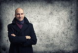 man in coat over cracked wall background