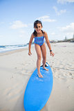 Cute young girl standing on surfboard