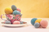 Brightly colored eggs in tea cup