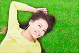 pretty woman listening music and lying on a meadow