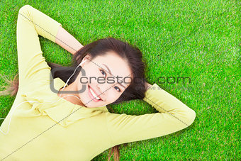 beautiful  woman holding head and lying on a meadow