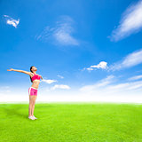 relaxing young woman standing on a meadow with blue sky