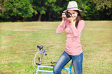 female photographer holding camera and sitting bike
