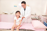 male pediatrician examining little girl in the clinic