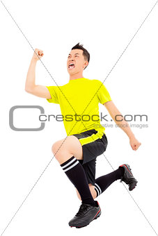 Excited young soccer player raised hand and kneeling down
