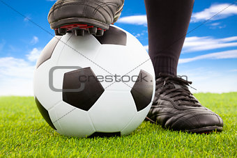 Soccer player's feet in casual pose on an open playing field