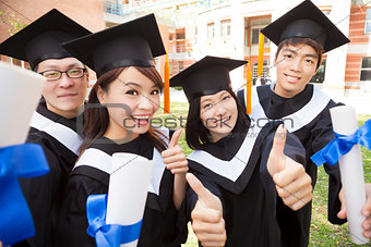 Group of graduating students holding diploma and thumb-up