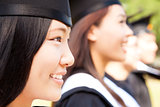 close-up smiling female university graduate  with classmates
