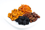 Isolated four heaps of dried fruits apricots, prunes, dates