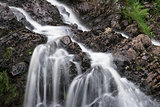 Landscape detail of waterfall over rocks in Summer long exposure