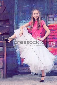 Beautiful girl in white skirt of tulle and a pink shirt