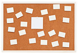 small sheets of paper on bulletin cork board