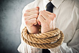 Businessman with hands tied in ropes