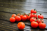 Fresh wet tomatoes on wooden table