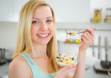 Happy young woman eating healthy breakfast