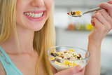 Closeup on happy young woman eating healthy breakfast