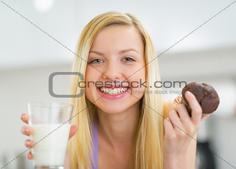 Portrait of happy young woman with milk and chocolate muffin in