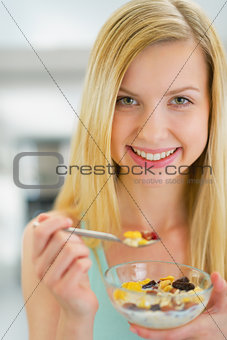 Portrait of happy young woman eating muesli in kitchen