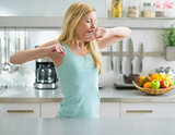 Young woman stretching after sleep in kitchen