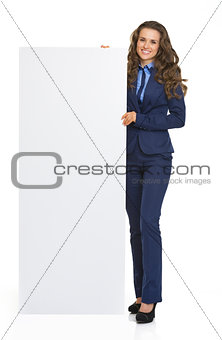 Full length portrait of happy business woman showing blank billb