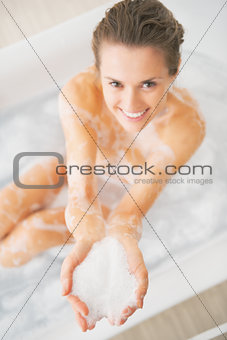 Closeup on smiling young woman in bathroom showing foam
