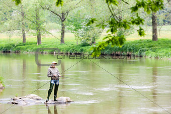 woman fishing in Sazava river, Czech Republic