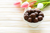 chocolate candy and flowers on wooden background