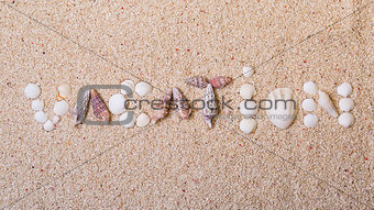 "Title ""vacation"" from sea shells with coral sand"