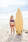 Young girl standing with surfboard on beach