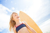 Happy young girl with surfboard at beach
