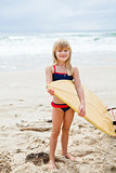 Smiling young girl holding surfboard on beach