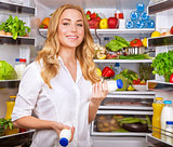 Woman chosen yogurt in opened refrigerator