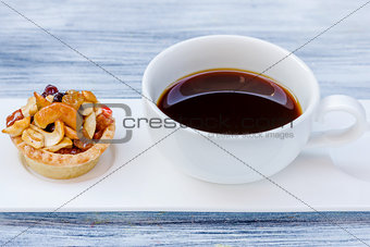 Black coffee and Fruit Tart  on wooden table