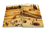 An opened old book with a picture Western Wall,Temple Mount, Jerusalem.Photo in old color image style.
