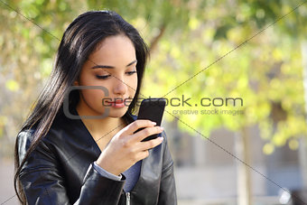 Beautiful woman texting on a smart phone in a park