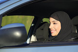 Happy arab saudi woman driving a car