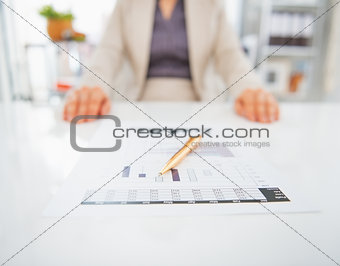 Closeup on document on table and business woman in background
