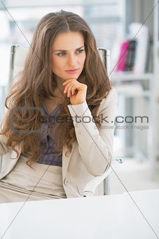 Thoughtful business woman sitting in office