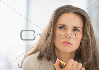 Portrait of thoughtful business woman with pen