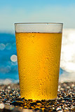 water drops on a glass of cold beer on the beach