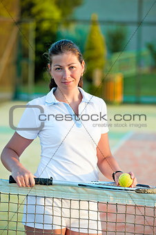 girl with a ball and a tennis racket at the net worth