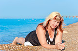 young beautiful grandmother resting on the beach