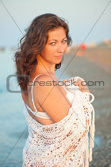 portrait of charming brunette in a white shawl at dawn
