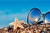Starfish and sunglasses on the beach against the sea