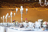 Wedding reception hall with decor including candles, cutlery and