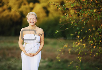 beautiful pregnant young woman in greek white dress outside