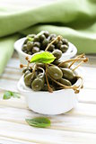 two kinds of pickled capers in white bowl on wooden table
