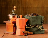 Still life of coffee beans and coffee maker on vintage wooden background
