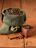 Still life of coffee beans in canvas sack on vintage wooden background